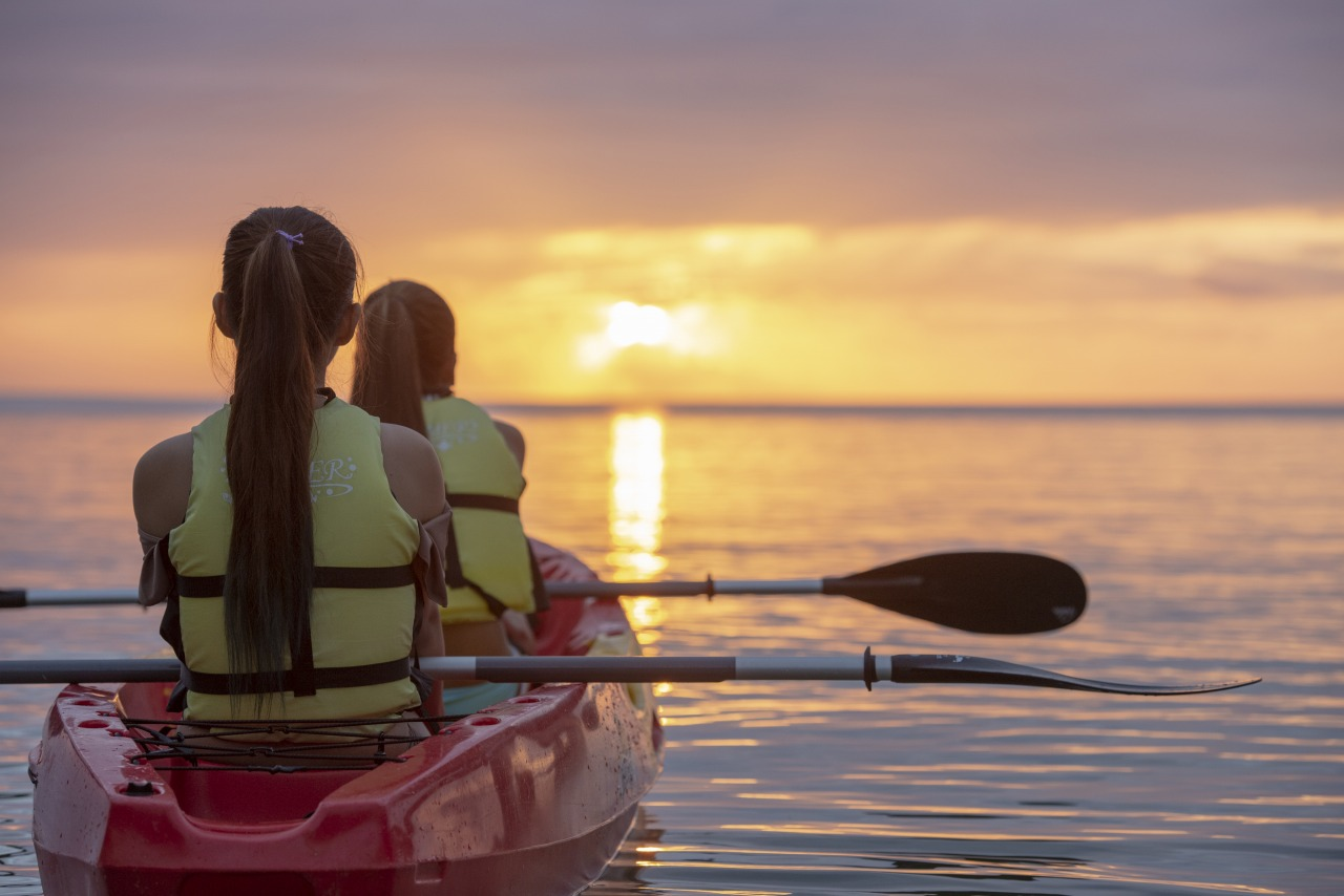 伊良部島方面に落ちる太陽を眺める女性