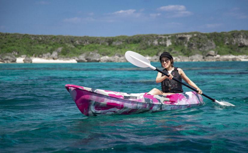 ターコイズブルーの海でカヤックを漕ぐ女性
